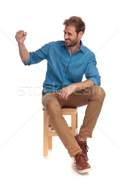 сидящий случайный человека смеясь кулаком вверх Сток-фото © feedough