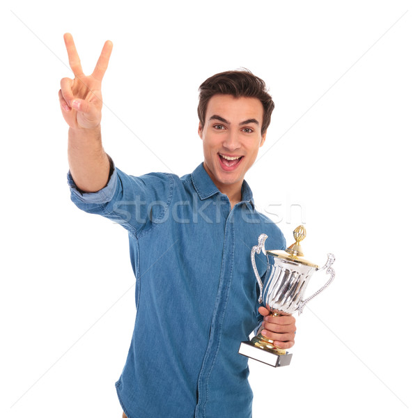 surprised  man winning  cup award and makes the victory sign Stock photo © feedough