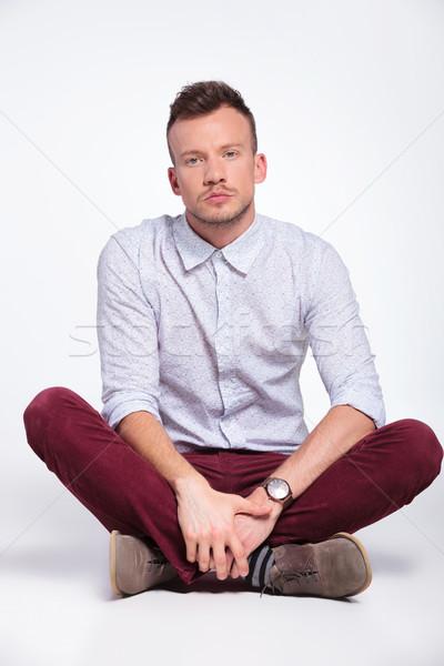 Homme jambes croisées jeune homme séance étage Photo stock © feedough
