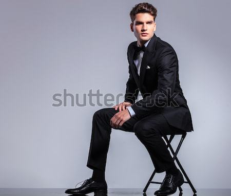 seated young man fixes his hair Stock photo © feedough