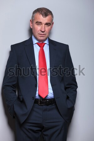 business man leaning on wall with hands in pockets Stock photo © feedough