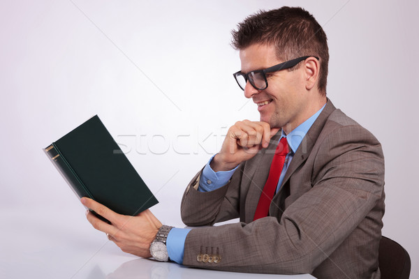 side of young business man reading a book with hand on chin Stock photo © feedough