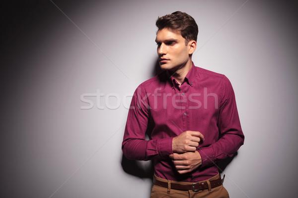 Jól kinéző fiatalember dől fal megjavít kabátujj Stock fotó © feedough