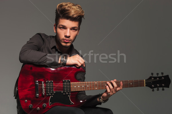 Stock photo: side view of a young man holding an electric guitar