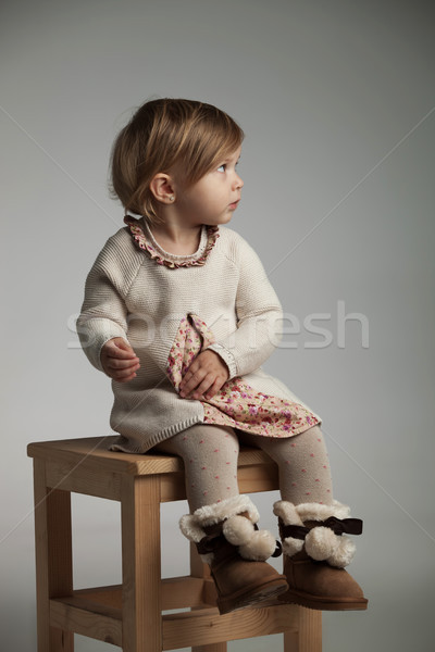 side view of a cute little girl sitting on  chair  Stock photo © feedough