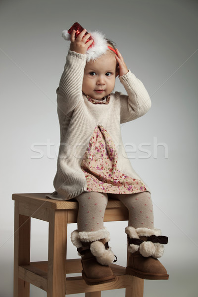little smiling girl is holding her christmas hat on head Stock photo © feedough