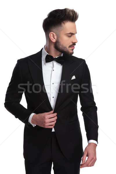 young man in tuxedo holds collar and looks to side  Stock photo © feedough