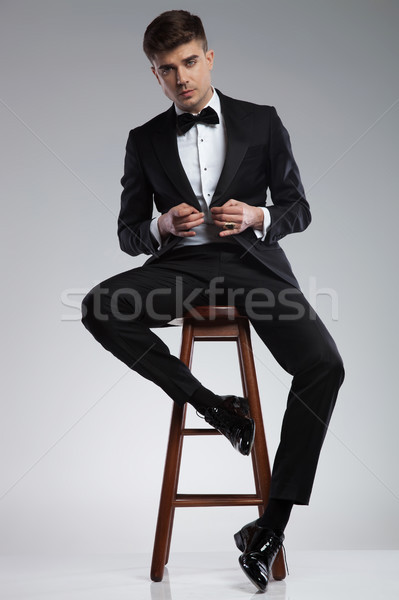 seductive businessman sitting and buttoning his black suit Stock photo © feedough