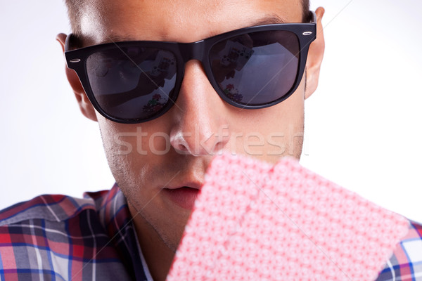 Young gambler with sunglasses holding his poker hand up Stock photo © feedough