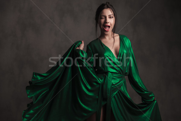 seductive woman holding her long green dress is winking Stock photo © feedough