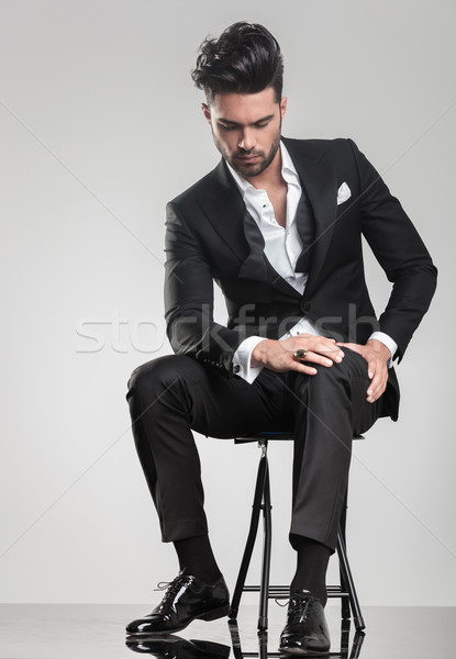 Elegant young man stitting on a stool while looking down Stock photo © feedough