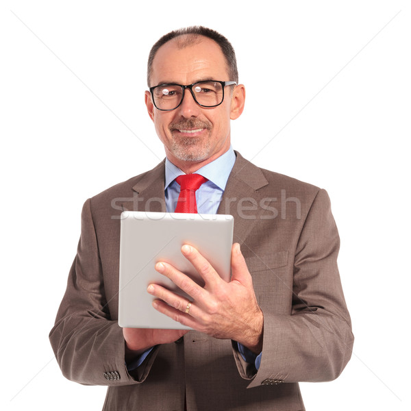 smiling old businessman holding a tablet pad computer Stock photo © feedough