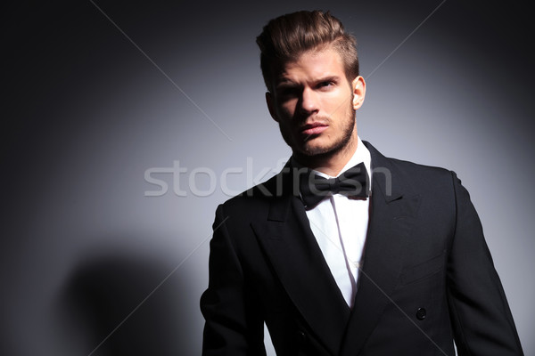 handsome man in tuxedo and bow tie in a dramatic pose Stock photo © feedough