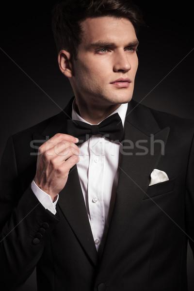 Handsome young elegant man fixing his bowtie. Stock photo © feedough