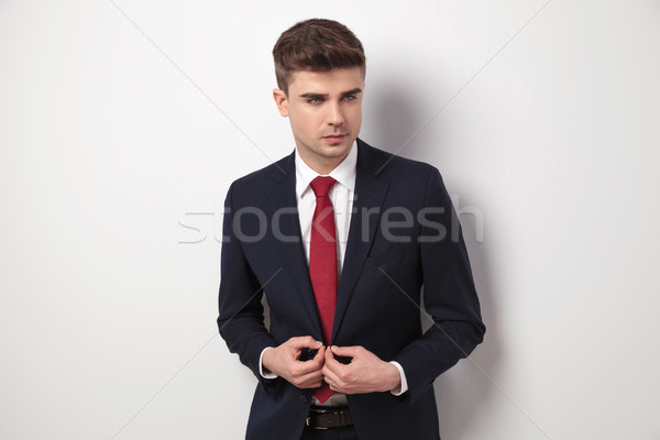 handsome businessman buttoning his suit jacket looks to side Stock photo © feedough