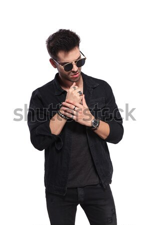 casual man fixes bracelets and looks down to side Stock photo © feedough