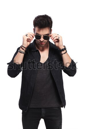 portrait of handsome man fixing sunglasses while looking down Stock photo © feedough