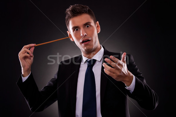 Young conductor sticking his baton in his ear Stock photo © feedough