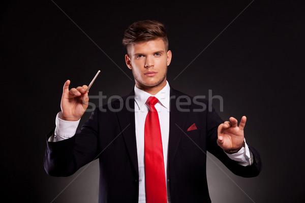 Homme d'affaires orchestre jeunes bâton regarder caméra Photo stock © feedough