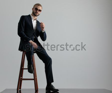 business man sitting on a stool arranging his jacket  Stock photo © feedough