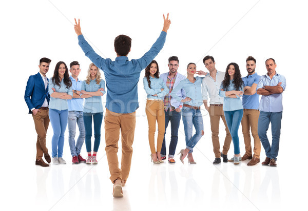 young casual man congratulates his colleagues with hands up Stock photo © feedough