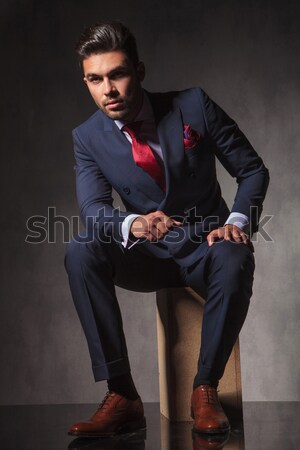seated young business man unbuttoning jacket Stock photo © feedough