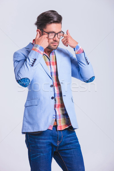 casual guy rubbing his eyes while wearing glasses  Stock photo © feedough