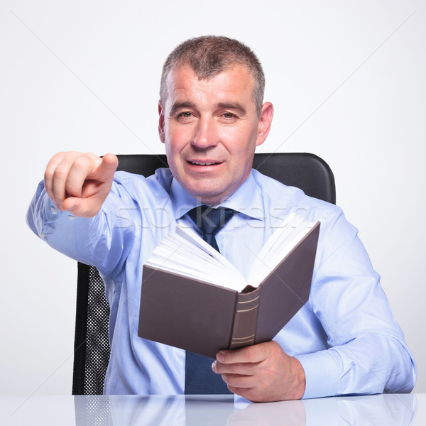 old business man pointig while holding book Stock photo © feedough