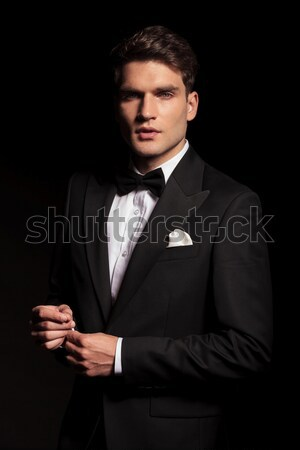 businessman in black suit with bowtie posing seated in dark  Stock photo © feedough