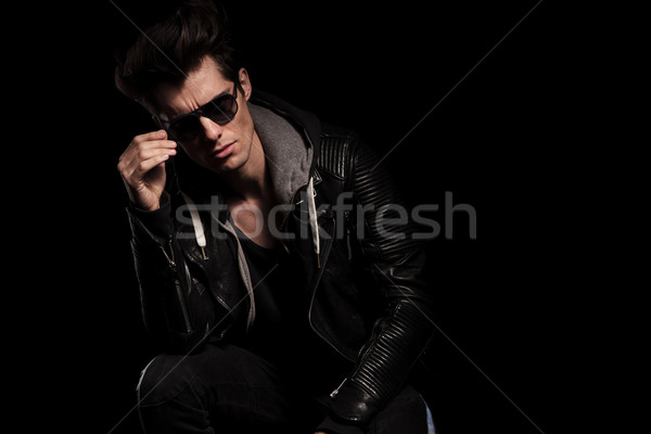young fashion model in leather jacket taking off his sunglasses Stock photo © feedough