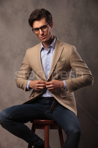 smiling business man sitting and unbuttoning his coat Stock photo © feedough
