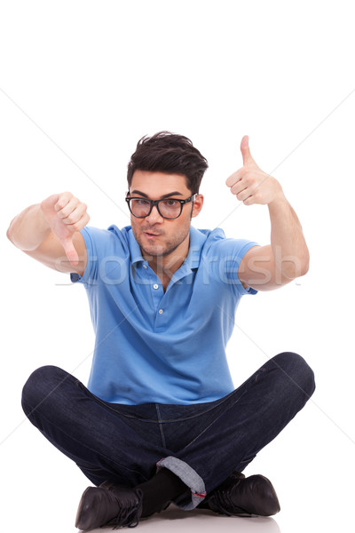 confused young man thumbs up and down Stock photo © feedough