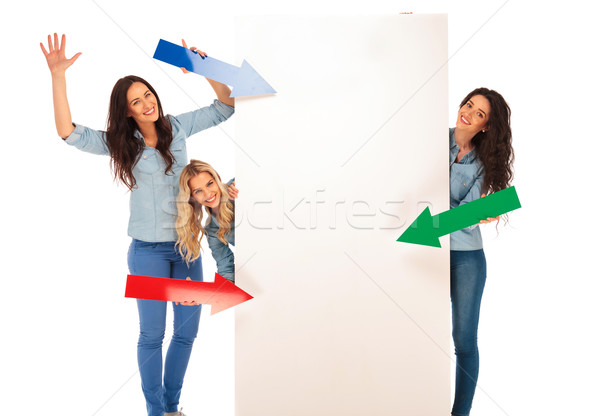 3 women pointing their arrows to a big blank board  Stock photo © feedough