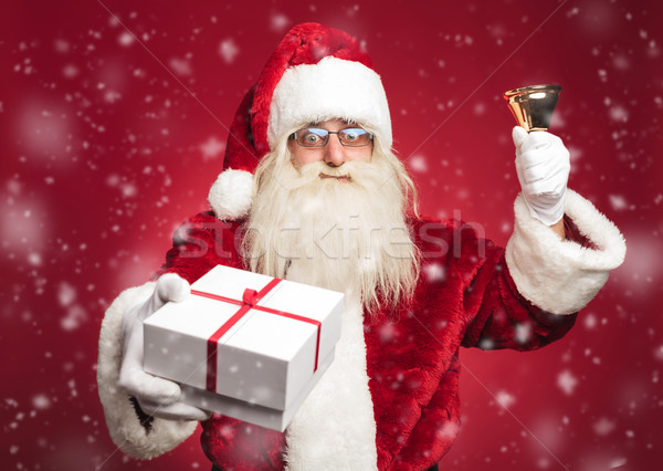 happy santa claus ringing his bell and offering a present Stock photo © feedough