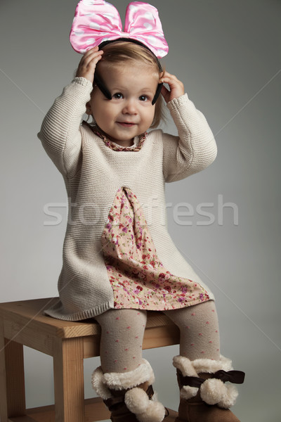 Stock photo: seated little girl putting on a pink bow headband