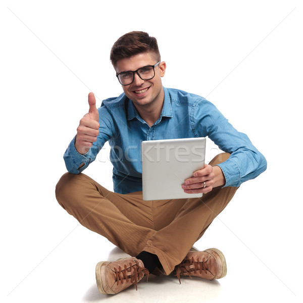 seated  student reading good news on tablet and makes ok  Stock photo © feedough