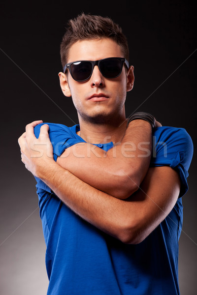 young casual man with hands crossed on his shoulders Stock photo © feedough