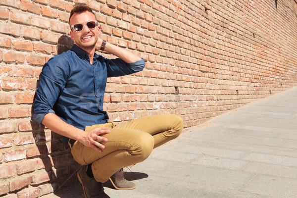 Toevallig man hurken muur glimlachend jonge man Stockfoto © feedough