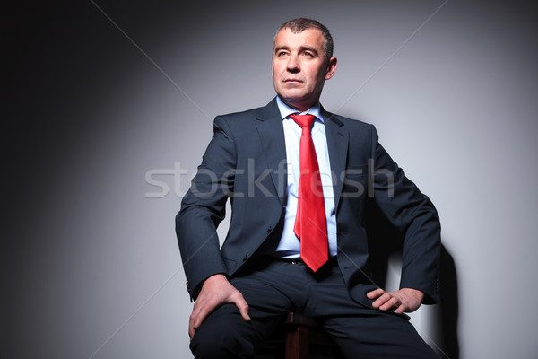 business man sitting on a stool, against grey background. Stock photo © feedough