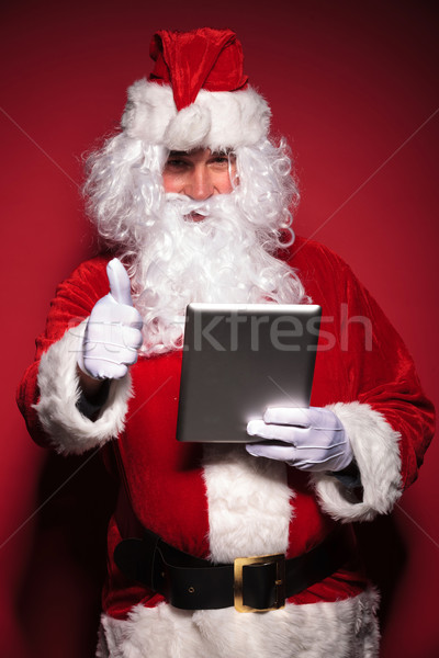 santa claus is reading about good news on his tablet pad Stock photo © feedough