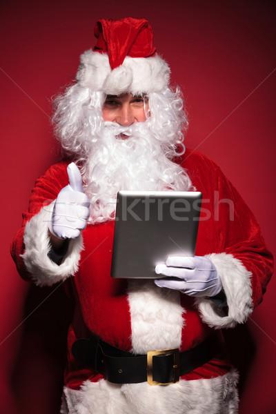 Papá noel lectura una buena noticia tableta ordenador rojo Foto stock © feedough