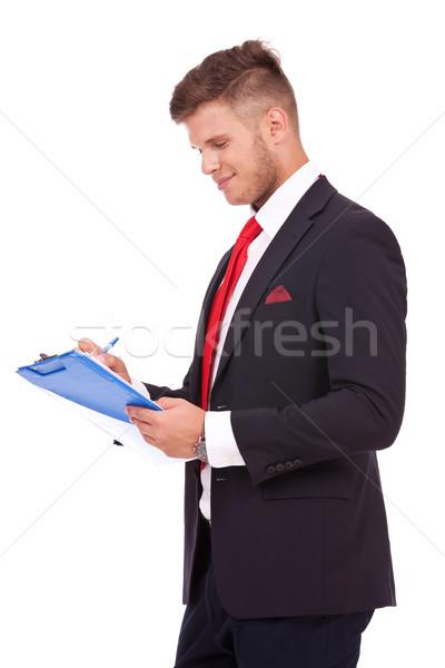 Hombre de negocios notas algo jóvenes portapapeles sonriendo Foto stock © feedough