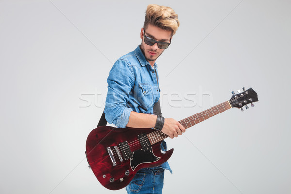 portrait of man looking down in studio while holding a guitar Stock photo © feedough