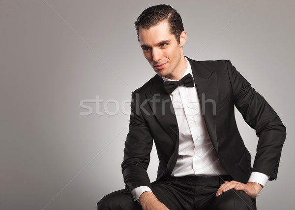 side view of a smiling seated young man in tuxedo  Stock photo © feedough