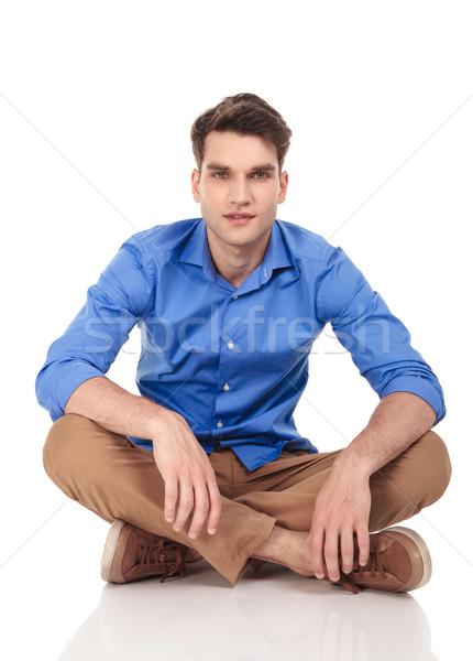 Bello giovane seduta gambe incrociate isolato sorriso Foto d'archivio © feedough