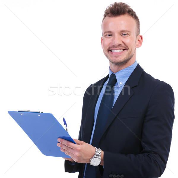 business man smiles with pen and clipboard Stock photo © feedough