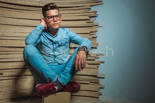 young man sitting in studio with legs crosses Stock photo © feedough