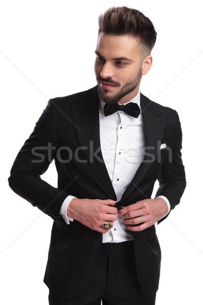smiling young man in tuxedo opening his coat Stock photo © feedough