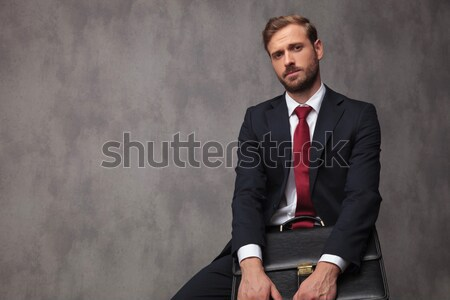 sexy gentleman dressed elegantly sitting and pointing to side Stock photo © feedough