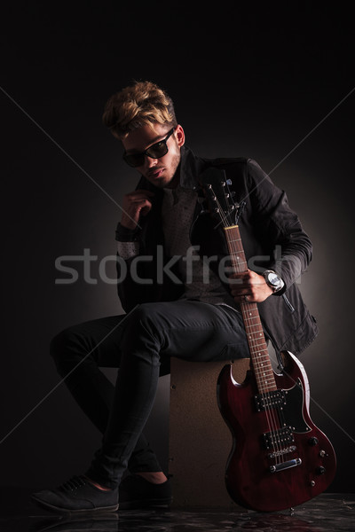 young guitarist sitting and holding his jacket by it's collar Stock photo © feedough